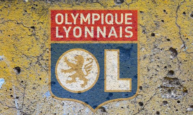 Logo de l'Olympique Lyonnais sur un mur criblé de trous et de lézardes.